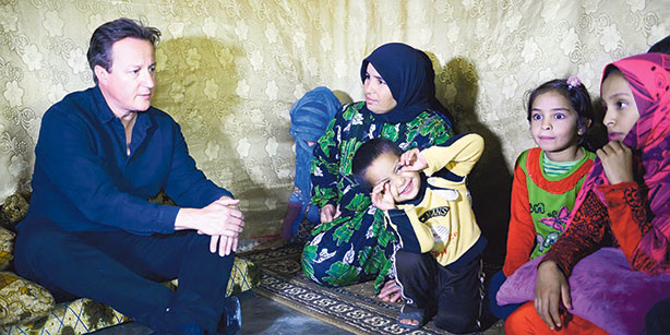 David Cameron looking uncomfortable while visiting a refugee camp in Lebanon recently. The kid in the picture knows exactly what to do...