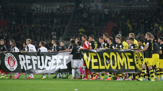 Soccer fans and clubs across Europe, particularly in Germany and especially F.C. St. Pauli, are extending a warm welcome and a helping hand to the thousands of refugees.
