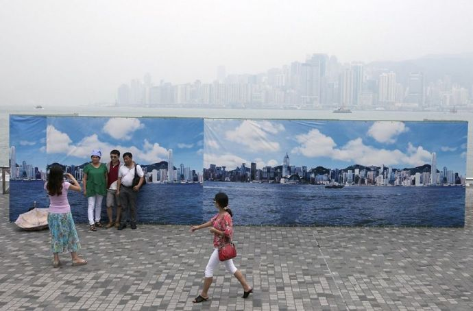 Tourists posing with the Hong Kong skyline.